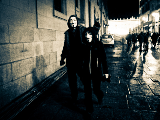 front page image: people with Guy Fawkes masks walking on a street at night